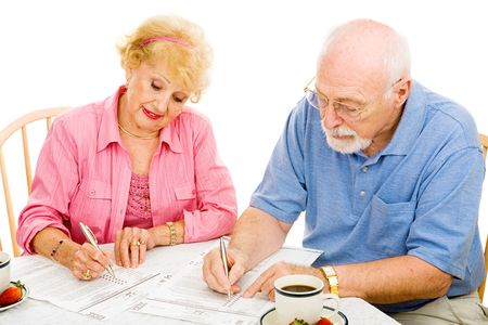 Senior couple filling out absentee ballots at home.  Isolated on white. photo