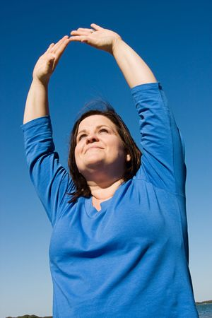 plus sized: Plus sized woman doing yoga outdoors and offering praise. Stock Photo