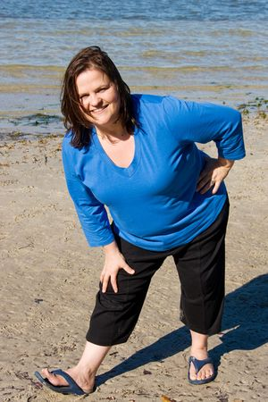 plus sized: Plus sized woman stretching on the beach as part of fitness program.