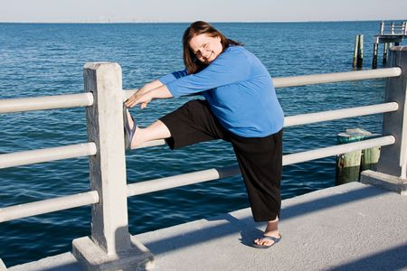 prior: Beautiful plus-sized woman stretching prior to going on an outdoor fitness walk.