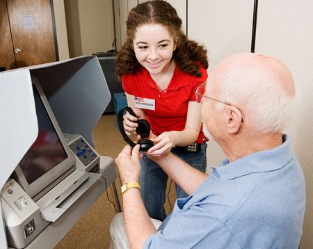 Helpful election volunteer provides headphones to assist a senior man in voting on new touch screen machine.   photo