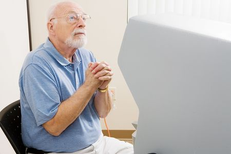 impaired: Senior man at the polls praying for guidance on how to vote.  Voting on the new florida touch screen for hearing impaired.   Stock Photo