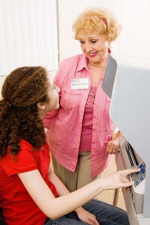 encuestando: Superior de lugar de votaci�n de voluntarios ayudando a los j�venes votantes.  Foto de archivo