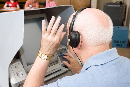 impaired: Senior man using a new touch screen voting machine equipped for hearing and vision impaired.  Election workers visible in background.