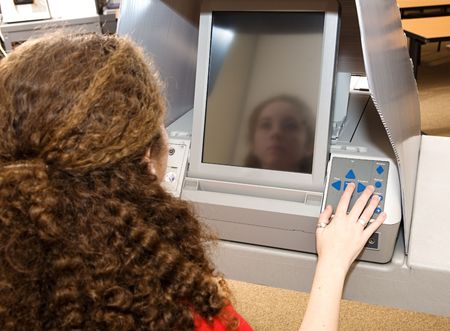 electronic voting: Eighteen year old girl voting for the first time on a touch screen machine.   Stock Photo