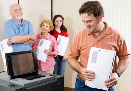 voting: Mid-adult man checking out the new optical scan voting machine at the polls.