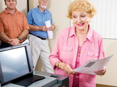 electronic voting: Senior lady voting on new optical scanning machine.