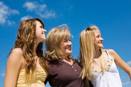 three generations of women: Beautiful grandmother & granddaughters laughing in profile against a blue sky.   Stock Photo
