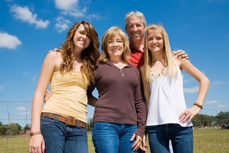 Grandparents and their beautiful teen granddaughters outside on the farm.   photo