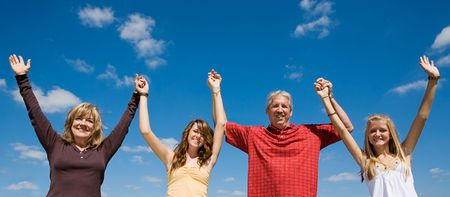 Beautiful family holding hands and raising their arms against a blue sky.   Stock Photo