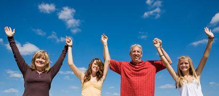 alabanza: Familia hermosa que lleva a cabo las manos y que levanta sus brazos contra un cielo azul.