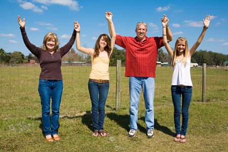 Beautiful family outdoors on their farm holding hands and raising their arms in praise and joy.   photo