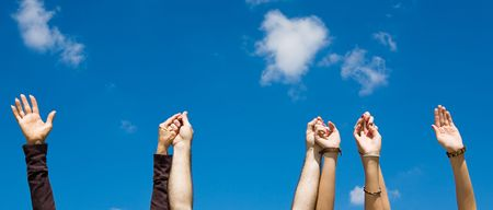 Hands raised and holding eachother against a blue sky.   photo