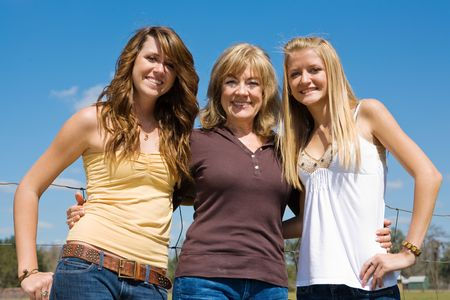 three generations of women: Beautiful young grandmother and granddaughters outdoors on their farm.   Stock Photo
