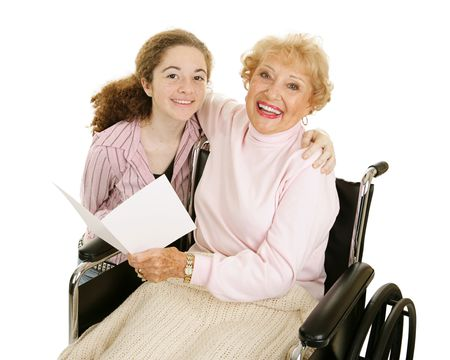 Teen girl gives greeting card to her grandmother for mothers day or other holiday.   Banco de Imagens