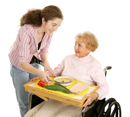 Teen volunteer brings a meal to an elderly woman in wheelchair.  Isolated on white. photo