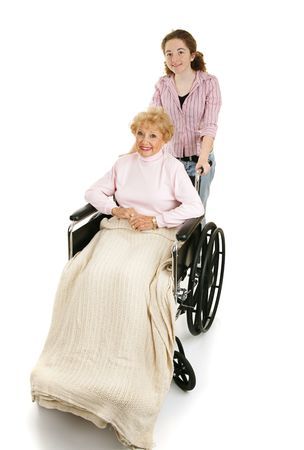 help: Teen girl pushing a disabled senior woman in a wheelchair.  Isolated on white.