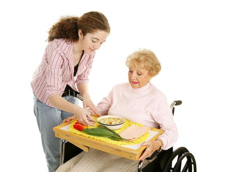 Teen volunteer brings lunch to a disabled senior woman.  Isolated on white. photo
