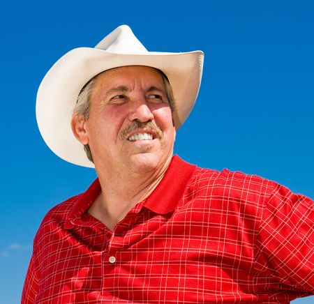 checkered polo shirt: Handsome mature cowboy looks off in the distance with pride and optimism.