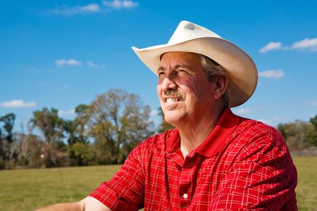checkered polo shirt: Portrait of a mature cowboy on his ranch, looking to the future.