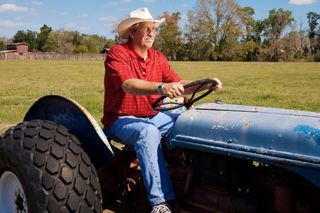 checkered polo shirt: Handsome mature cowboy riding his tractor through his fields.