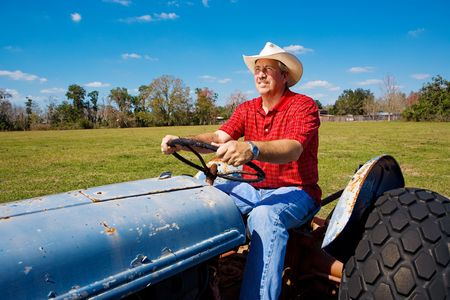 Handsome mature farmer on his tractor, mowing the field.   photo