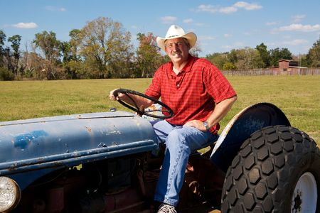 checkered polo shirt: Handsome mature farmer rides his tractor Stock Photo