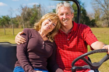 Good-looking retired couple riding their property in an all terrain utility vehicle.   Stock Photo - 2748051