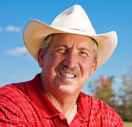 checkered polo shirt: Portrait of a handsome, mature cowboy outdoors.   Stock Photo