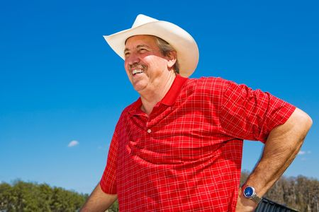 checkered polo shirt: Handsome mature cowboy laughing against a blue sky, with room for text.