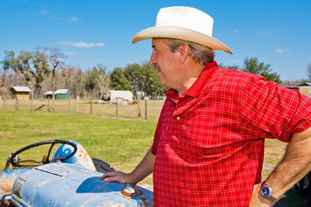 checkered polo shirt: Handsome mature rancher leaning on his tractor and surveying his property.