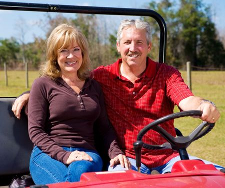 retired couple: Fit youthful retired couple riding an all terrain vehicle.