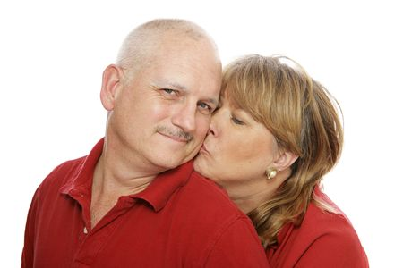 Happy middle aged man receiving a kiss from his wife.  Isolated on white.   photo