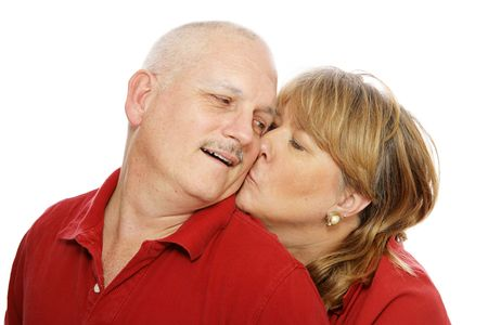Middle aged couple isolated on white.  Wife is kissing husband on the cheek.   photo
