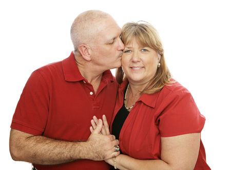 Attractive middle-aged couple in love.  Hes kissing her on the cheek.  Isolated on white. Stock Photo