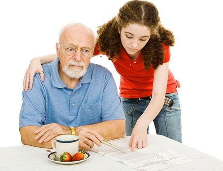 alzheimers: Confused senior man trying to fill out an absentee ballot with his granddaughters help.  Isolated on white.