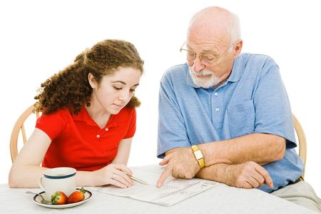 absentee: Teen girl filling out absentee ballot gets help from her grandfather.  Isolated on white. Stock Photo