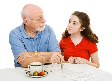 Grandfather explains democracy to his teen granddaughter while filling out his absentee ballot.  Isolated on white.