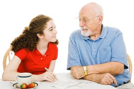 祖父は孫娘 (不在者投票) の書類の記入を助けます。 白で隔離。 写真素材