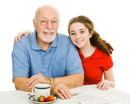 Teen girl and her grandfather at the table filling out paperwork together.  Isolated on white. photo
