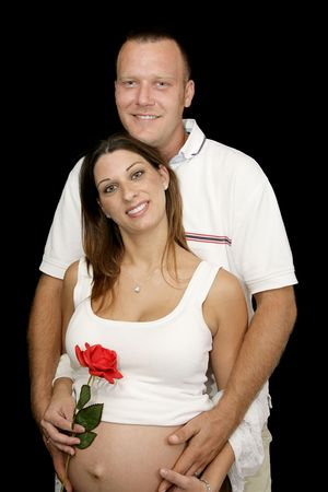 Portrait of happy, smiling pregnant couple against a black background.   photo
