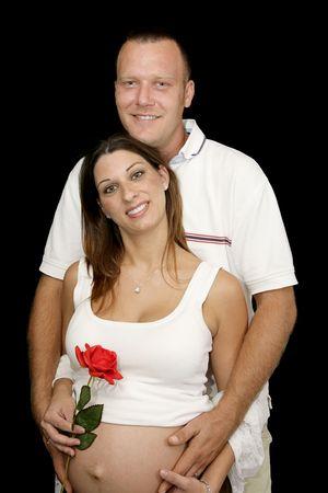 Portrait of happy, smiling pregnant couple against a black background.   photo