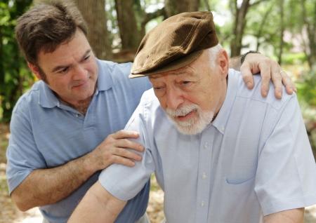 Hombre mayor en salud que falla y su hijo de mediana edad preocupado. Foco en hombre mayor.