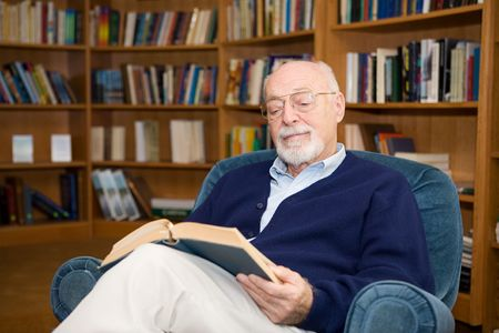 mature student: Handsome senior man relaxing with a good book.  Plenty of room for text.   Stock Photo