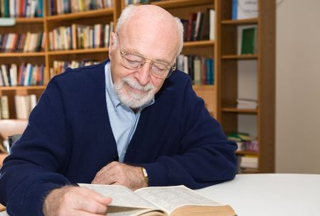 enjoys: Senior man enjoys a good book in the library.  Horizontal view with room for text.   Stock Photo