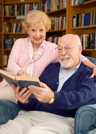 Happy senior couple reading together at the library.   Stock Photo
