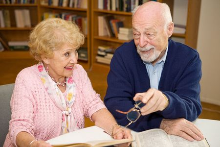 Senior man and woman meeting at the library and discussing books.   Stock Photo - 2834903