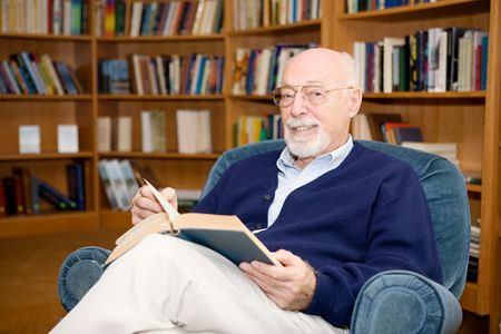 Intellectual looking senior man reading a book in the library. Stock Photo - 2834900
