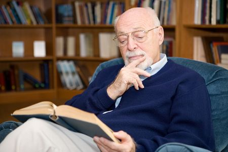 Closeup of senior man sitting in an easy chair and reading.   Stock Photo - 2834898
