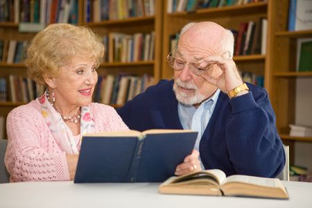 Senior woman at the library, showing her husband a passage in a book.   Stock Photo - 2834902